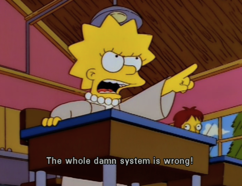 "[Description: Screencap of Lisa Simpson sitting at a desk, pointing her finger and yelling ""The whole damn system is wrong!""]"