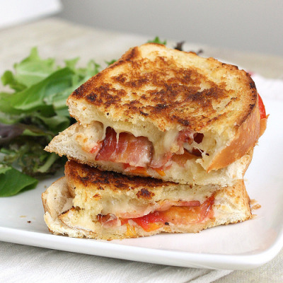 breakfast-brunch-dessert:  Garlic Rubbed Grilled Cheese with Bacon and Tomatoes 8 slices bacon  3 oz (about 1 1/4 cups) grated Gruyère  3 oz (about 1 cup) grated fontina   2 tablespoons finely grated Parmigiano-Reggiano   1/4 teaspoon crushed red pepper flakes (or to taste)   8 1/2-inch-thick slices Italian bread   2 medium ripe tomatoes, cut into 1/4-inch-thick slices   2 tablespoons butter, at room temperature   1 to 2 large cloves garlic, halved and peeled for rubbing Directions Cook the bacon in a heavy-bottomed skillet until browned and crisp. Remove to a paper towel-lined plate. Pour off the grease from the pan and wipe clean.   Combine the cheeses and red pepper flakes in a small bowl. Lay 4 slices of the bread on your work surface, and distribute half of the cheese evenly among the bread. Top the cheese with 2 slices of bacon and then 2 or 3 slices of tomatoes (enough to cover the cheese and bacon). Evenly distribute the remaining cheese among the 4 sandwiches. Lightly butter one side of the remaining four slices of bread, and put them on top of the sandwiches, butter side up.   Heat your heavy-bottomed skillet over medium heat. Place the sandwiches butter side down in the pan and cook on the first side until the bread is golden brown and toasted. Meanwhile, butter the top slice of bread on each sandwich. Flip the sandwiches using a spatula and continue to cook on the other side until the bread is golden brown. You can use the spatula to compress the sandwich as it cooks on the second side. Remove the sandwiches from the pan and immediately rub both sides with the cut side of a garlic clove. Cut the sandwiches in half and serve.