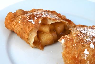"breakfast-brunch-dessert:  Fried Apple PiesTart shell:  1 cup unbleached all-purpose flour  6 tablespoons cold butter  1/4 cup ice water  1/2 teaspoon salt  1 teaspoon sugar Filling: 2 cups peeled apples, chopped to 1/2"" squares  1/2 cup apple cider  1/4 cup sugar  1 teaspoon cinnamon  zest and juice of 1 lemon  big pinch salt  2 tablespoons flour Directions In the bowl of your food processor, combine the flour, salt, and sugar by pulsing 3 times. Cut up the butter into large chunks, and add to the flour. Pulse several times, until the mixture is sandy and crumbly. Drizzle in the ice water, and pulse 2 or 3 times until the dough just holds together.   Turn the dough out onto a lightly floured surface and form into a 6"" disc. Wrap the disc tight in plastic wrap and refrigerate for at least 30 minutes.  Meanwhile, make the filling. Combine the apples, cider, sugar, zest and juice, and salt, and cook over medium heat. The mixture will bubble, and cook down. After about 15 minutes the apples will soften, but still have a little texture. Stir in the flour and cook for a minute or two more. Remove from heat and set filling aside to cool.   Either in an electric skillet, deep fryer, or heavy-bottomed pan with deep sides, heat a neutral cooking oil to 350 degrees.  On a lightly floured surface roll 1/3 of the dough into a 10 – 12"" oval. To make the first two pies, cut the oval in half, and carefully pile 1/3 cup of filling on one half of each semi-circle. Quickly wet the edges, and fold over, pressing each into a turnover shape. Seal the edges with the tines of a fork. Fry the pies for a total of 3 – 4 minutes, flipping them halfway through. Remove from oil when the pies are a deep golden brown. Place on a stack of paper towels, dust with confectioners sugar and serve. Follow these steps for the other four pies."