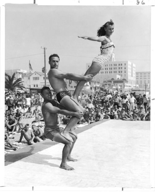 "Sept. 6, 1954  Santa Monica's Muscle Beach crowds were treated to the show they have come to expect Labor Day weekend. DeForrest Most, 37, is bottommost in this typical pyramid pose that also includes Art Kidder, 37, and Sandra Hollabaugh, 14.  (via the book ""Imagining Los Angeles: Photographs of a 20th Century City,"" published by The LA Times in 2000. Credit: Bill Beebe / Los Angeles Times)"