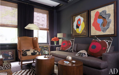Abstract '70s silk-screens hang above the sofa by Peter Carlson from Billy Baldwin Studio, where Wallis, a pug, naps; the den's walls are painted in Tanner's Brown by Farrow & Ball.