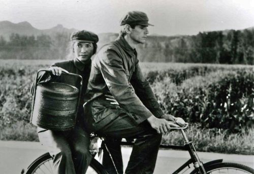 John Lone and Jeremy Irons ride a bike.
