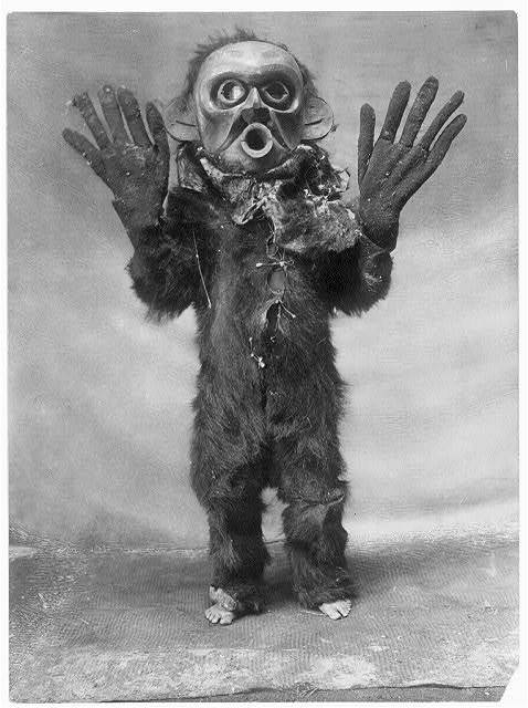 "1910s A Koskimo person wearing full-body fur garment, oversized gloves and mask of Hami (""dangerous thing"") during the numhlim ceremony. Notice the feet. (via Library of Congress and dreams like that)"