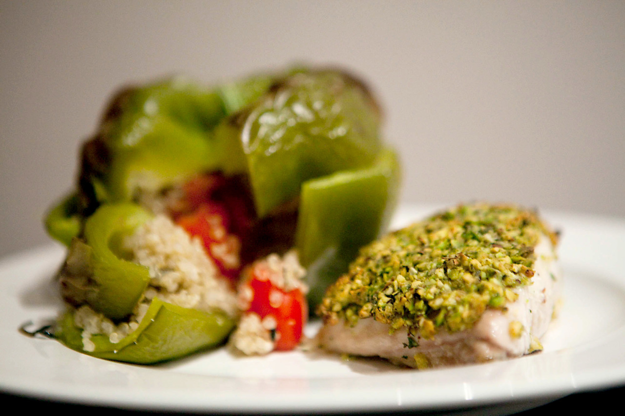 Pistachio and Oregano Crusted Snapper with Quinoa Stuffed Pepper I usually wouldn't buy pre-packaged fish, but it looked fine so I went for it.  Meh.  Kind of a waste of an awesome recipe, but on fresh fish this would be killer.  Oh, and maybe pan-seared instead of baked.  Who needs health. Ingredients (peppers): 2 green peppers, lids sliced off and centers removed 1 cup quinoa 2 cups of water 1 punnet of grape or cherry tomatoes 1 portabello mushroom, diced 2 garlic cloves, chopped 3 tbsp fresh thyme Salt, pepper and olive oil Boil quinoa in the water, stirring to make sure it doesn't stick or burn.  When finished, toss in everything but the peppers, seasoning with a bit of salt, pepper, and olive oil to taste.  Fill the peppers (there will be leftovers), put the lids on, and bake for 30 minutes at 200C / 375F. Ingredients (fish): 1/2 cup pistachios 1/4 cup oregano leaves Juice and zest of half a lemon Salt and pepper 2 garlic cloves 2 tbsp olive oil 2 big or 4 smaller pieces of snapper In a food processor, grind up everything but the oil and fish.  Don't grind it to a pulp, just pulse.  Use the oil to coat the fish, and then top with the nut mixture.  Bake for 15 minutes, under the grill, at 200C / 375F.  Or just fry it, it'll taste better. If you haven't yet, it'd be swell if you could take a minute and vote for my blog for the pedestrian.tv Blogster Awards.  Pretty please?