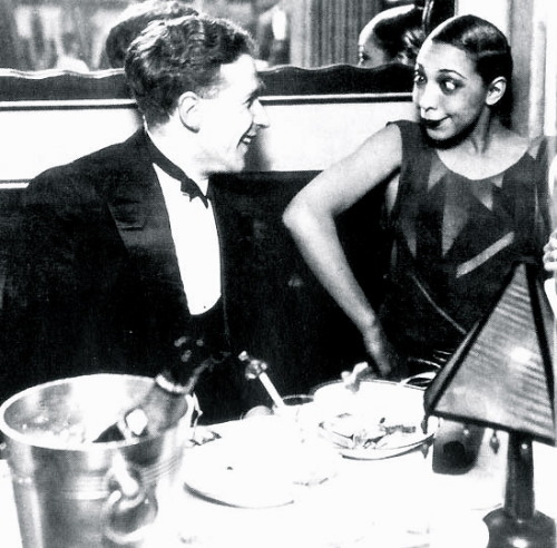 Author Georges Simenon with Joséphine Baker at La Coupule, Paris, 1925 (via nyrbclassics) in honor of the publication of Act of Passion, a photo of Simenon and onetime paramour, Josephine Baker (champagne bottle chilling in bucket.)