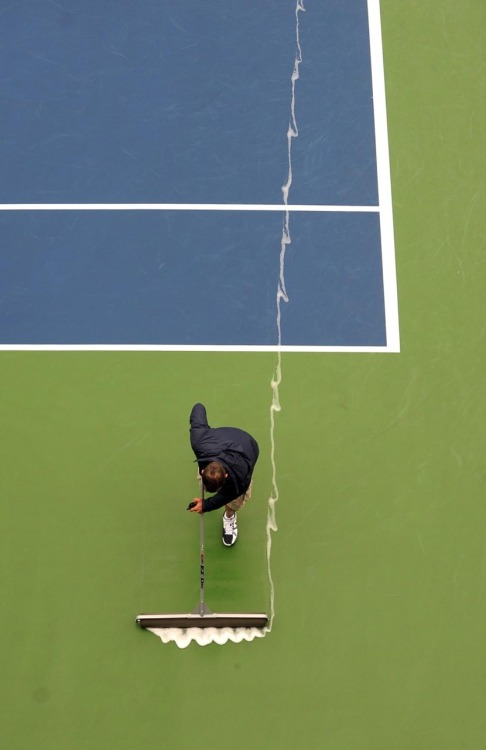 inothernews:  SWEEP VICTORY   A worker used a squeegee to clean the court at Louis Armstrong Stadium  during the U.S. Open tennis tournament in Queens, N.Y., Wednesday.  (Photo: Justin Lane / EPA via the Wall Street Journal)