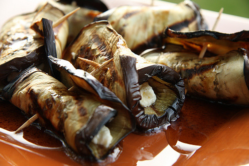 Grilled Eggplant Rolls with Mint and Garlic Dressing 2 large eggplants 3 tablespoons olive oil 1 teaspoon sea salt  dressing   2 garlic cloves 2 tablespoons red wine vinegar 2 tablespoons extra virgin olive oil 1 cup mint leaf (loosely packed) Extra* I tried this and added crumbled feta cheese in the middle before rolling, though you may like mozzarella or tomato sauce as well Slice the eggplant thinly. Brush each slice with olive oil and place on a ridged grill plate or barbecue. Turn when the cooked side has some good marks on it. Remove when the slices are they are soft and sprinkle with sea salt. Make the dressing by finely chopping the garlic and mint and mixing with the vinegar and olive oil. The wet ingredients will only coat the mint. Spread a little of the dressing on each slice of eggplant and roll it up. Drizzle any remaining dressing over the rolls. Serve at room temperature.  *If eggplant is usually too bitter for you, try salting each side of the slices and letting sit for half an hour before rinsing and drying off before seasoning and cooking. Continue with recipe after this. Makes six servings, 150 Calories each.