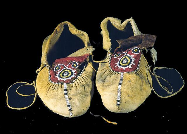 Moccasins, circa 1860-1890 These moccasins were made in the Great Lakes area. They are of cut and sewn deerskin and have soft soles. The flap is covered with red and white wool trade cloth onto which yellow, black, and white seed beads are sewn in a curvilinear motif. Green and white seed beads border the flap, and a band of black and white seed beads extends from it to the tip of the toe. There are skin ties attached to each side of each moccasin. There may have been hard soles attached to the soft soles at one time. Collection of the Illinois State Museum (via thisbeadifulworld:)