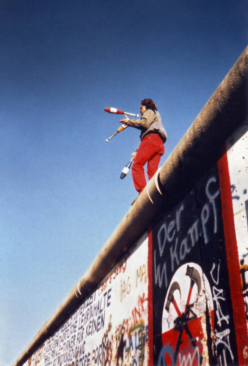 "picturesofwar:  A German man juggling atop the Berlin Wall a week after its falling and the opening of checkpoints between East and West Berlin. The wall was known by East German officials as the ""Anti-Fascist Protection Rampart"", while some West German officials referred to it as the ""Wall of shame"". November 16, 1989."