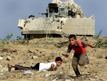 wakeupthedrones:  Palestinian children taking cover from live ammunition shot by Israel  no whizzing bullets no blood the cameraman seems to be safe the gun in the background is pointing in a different direction if there is another gun on the tank, it is not aimed low enough to be attacking the children no israelis on the scene i can also run and pretend to fall propaganda propaganda