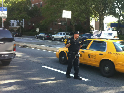 A uniformed police officer monitors traffic at the Brooklyn entrance to the Brooklyn Bridge Friday morning. Mayor Michael Bloomberg asked New Yorkers to be vigilant but go about  their business Friday despite a credible but unconfirmed terror threat  to coincide with the 10th anniversary of the September 11 attacks  involving New York or Washington.