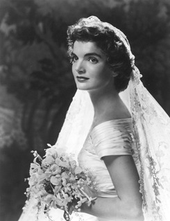 What the bride wore - Jacqueline Bouvier's ivory silk wedding gown required 50 yards of ivory silk taffeta and took more than two months to make. It was the creation of Ann Lowe, an African-American dress-maker born in Grayton, Alabama, who had designed gowns for the matrons of high society families. Ms. Lowe was 54 when she designed the Bouvier wedding dress, which featured a portrait neckline and bouffant skirt decorated with interwoven bands of tucking and tiny wax flowers. She also designed the pink faille silk gowns and matching Tudor caps worn by the bridal attendants.  Jacqueline wore her grandmother's heirloom rosepoint lace veil, attached to her hair with a small tiara of lace and traditional orange blossoms. She also wore a single strand of family pearls, a diamond leaf pin, which was a wedding present from Ambassador and Mrs. Joseph P. Kennedy, and a diamond bracelet the groom had presented to her the evening before the wedding. She carried a bouquet of white and pink spray orchids and gardenias. Jacqueline Kennedy's oral history interviews from 1964 will be published this week after being sealed from the public by her request.  More - Jacqueline Kennedy: Historic Conversations