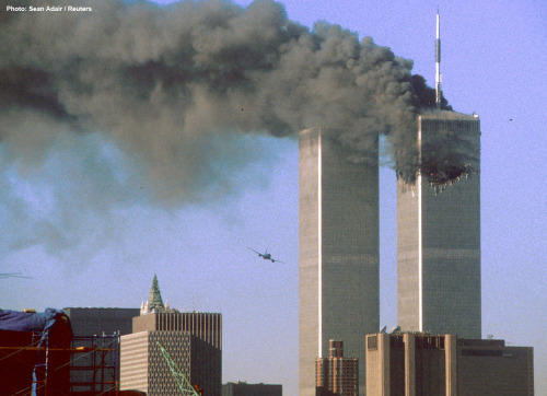 9:03 AM - September 11, 2001 United Airlines Flight 175 flies low toward the South Tower of the World Trade Center, shortly before slamming into the structure. The north tower burns after an earlier attack by a hijacked airliner in New York City, on September 11, 2001. Photo: Sean Adair/Reuters