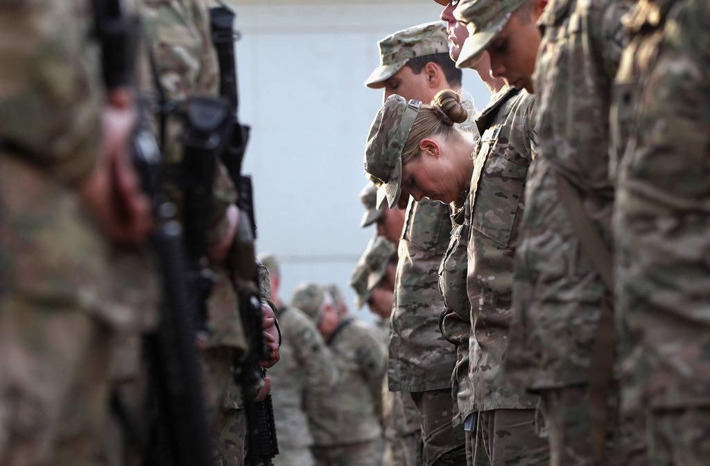 A Soldier in Afghanistan Bows Her Head on 9/11/11 by Trent Gilliss, senior editor  At Bagram Air Field, Afghanistan, a U.S. soldier bows her head during a prayer on a solemn, tenth anniversary ceremony of the terrorist attacks on September 11, 2001. (photo: John Moore/Getty Images)