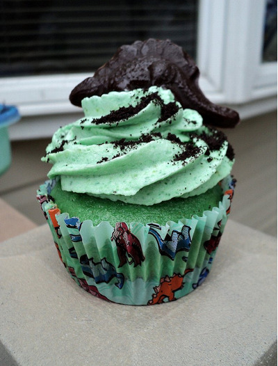 Check out the adorable dino cupcake that Jessica at Bake the Day made! How adorable is that!? And more importantly, delicious! I'll marry her and that damn cupcake, even if I have to move to Hawaii to do it! Especially if I have to move to Hawaii to do it! Actually, that might be my new game plan. Jessica says: I made them long before the East Coast had its great blackout recently with Hurricane Irene and sadly I had to throw out a few when our electric stopped the fridge [Ed.: NOOOO!!!]. They are a vanilla cupcake with a chocolate cookie crumb bottom and a ganache center, with vanilla buttercream and specks of colored sugar throughout, and a chocolate dino chilling out on top. Everything is homemade, and the cupcake was supposed to be grass, soil, and magma center, respectively. Hope you enjoy it! Um, we do. WE DO.