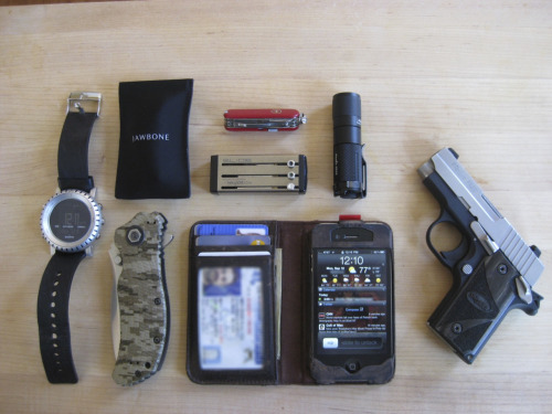 submitted by Omer B  I've been hanging out in another well regarded EDC based forum for years.  I recently found blog this while browsing flipboard on my iPad. figured its my turn.  Especially since I have one EDC item that I have never seen on here…  Here is my setup: Suunto Core Alu watch.  Wrist.Zero Tolerence 300DW TAD Gear edition flipper.  Clipped to right pocket.Jawbone (Only when I drive).  Right pocket.My SAK of the day (mini champ).  Sometimes I may carry an Atwood or something else fun instead of this. Right pocket.Keyport Slide - includes all my daily keys, a light, and a 16GB usb memory stick. Lighter Pocket.Fenix PD20+ . Sometimes bottom of right pocket &  sometimes clipped to belt.Sig Sauer P238 .  Carry IWB.Twelve South iphone wallet - Look it up.  It looks like a beautiful leather-bound book.  Inside its my iPhone and wallet.  Haven't seen many usable phone wallet combos on here. I keep this in my left pocket.  Editor's Note: Cool gear, how do you like that KeyPort? I think it might be great for some but I wonder how well it carries, especially since I don't think they come with a pocket clip or sturdy ring attachment point (I'd normally expect to see the SAK on a set of keys but here it's clearly different). Nice choices on the light, watch, knife and CC, too. You're right about the wallet — there haven't been too many on the site. I can definitely see the appeal of grabbing one item and having both your wallet and your phone with you (unless you forget your wallet, then you'd forget your phone too haha), but at the same time I'd rather keep them separate… Anyway, it looks good. Thanks for sharing!