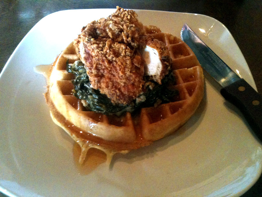 "Fried Chicken and Waffles at Market Garden Brewery in the Ohio City neighborhood of Cleveland, Ohio Boneless Fried Chicken, Creamed Collards, Sausage, and Spicy Honey; all on top of pillow-y Waffle My cousin works at this place and does everything from being the first person you see when you walk in the door to being the guy that cleans your table after you leave. But all nepotism aside, I really liked this place. First, I love the ""Market District"" they're building around the West Side Market. Tons of great restaurants and urban farms, as well as parks and a bunch of other ways to spend an afternoon. The kitchen must have finally worked out some of the kinks people had complained about, because everything we had was delicious. I told the waitress that any time I see Chicken & Waffles on a menu, I have to get it. After completely devouring everything on my plate, I realized that I much preferred this to The Sugar Factory's version. The collards added a savory bite that balanced out the sometimes overwhelming sweetness; with the only real problem being that the waffle got soggy by the end. Still a really, really good brunch. I can't wait to go back with some friends and have a few too many beers. This place is just awesome."