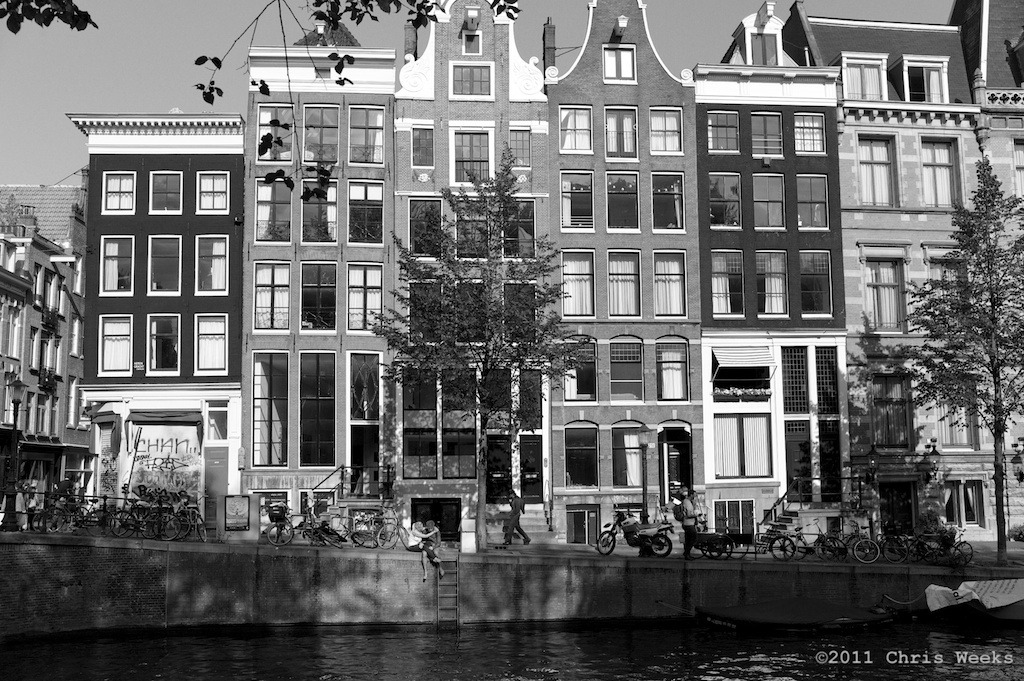 Amsterdam, The Netherlands:  July, 2011.  Compared to such tall homes, the couple is so small.  Beyond the fact I think humans give land/cityscapes scale … I like it even more when they're having a moment!  Leica M9.  35 'lux.  Aperture » Silver Efex Pro 2.
