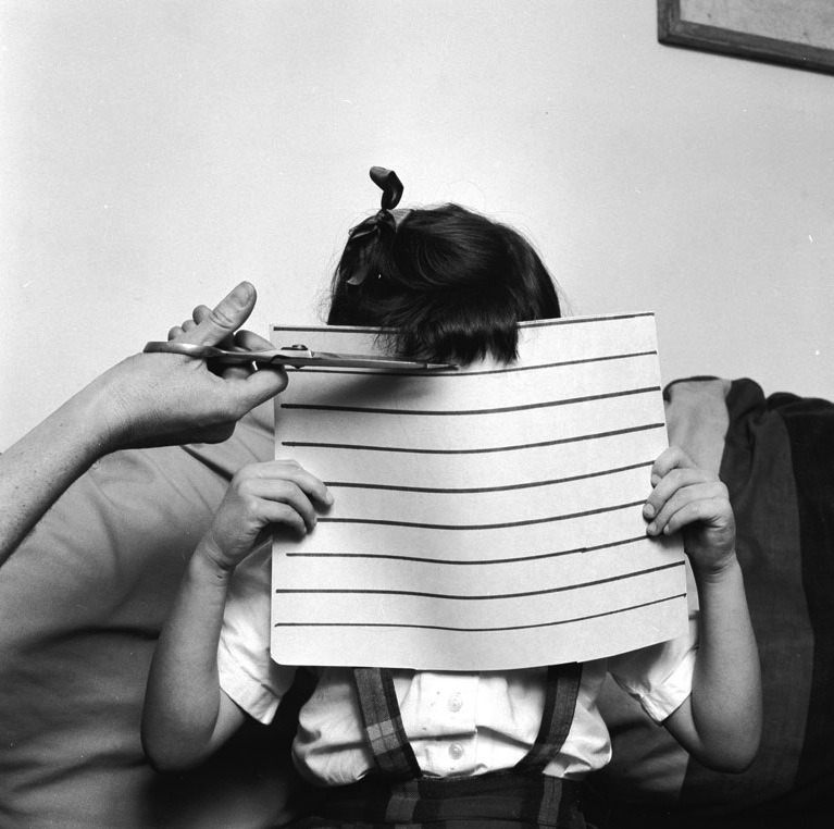 A young girl holds up a piece of cardboard to ensure that her mother cuts her fringe straight, circa 1955.