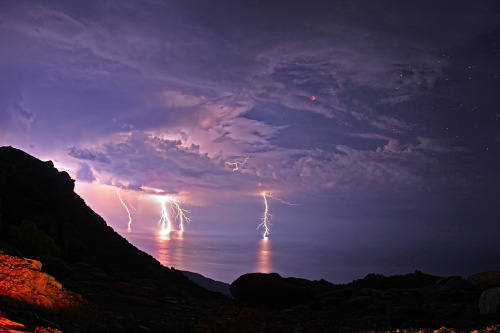 "scienceisbeauty:  Cloud-to-ground lightning drilling the Aegean Sea from a sky that includes the totally eclipsed Moon. It was taken on the night of June 15, 2011 from Ikaria Island during a thunderstorm. Credit: Chris Kotsiopoulos Source: Lightning and Lunar Eclipse, The Earth Science Picture of the Day  I think some of the GOP presidential candidates might take this as a sign of the ""End Times"""