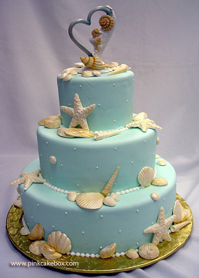 Beach Themed Wedding Cake  The beach theme wedding is well represented in this wedding cake. It's  covered in pale blue fondant and decorated with white and gold seashells  and sugar pearls. Each layer is lemon cake with lemon buttercream and  raspberry chambord buttercream.