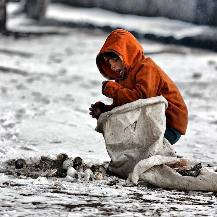 Homeless Afghan boy hurts his finger while collecting pile of broken glasses and bulbs.