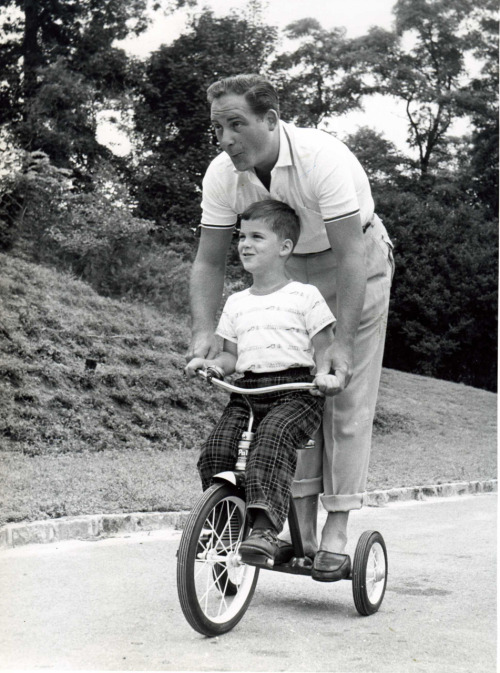 Sid and Ricky Caesar ride a trike.