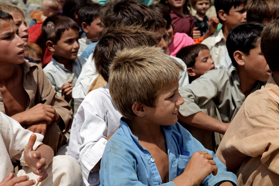 Afghan children gather to receive food, water, and school supplies from  U.S. Soldiers. The humanitarian assistance was distributed by Soldiers  from 1st Battalion, 32nd Infantry Regiment while on mission in the  Shigal district center, Konar province, Afghanistan, Aug. 19, 2009