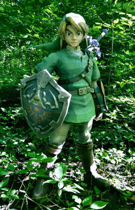 orangedrinks:  Lifesize Papercraft Link Created by DeviantARTist stuioofmm (aka Michaela Something)  Link is a life size papercraft model standing around 5'5. He is made completely from 250 gsm paper (about 4x stronger then normal paper). He has foam core supports in the top and bottom of his pants, top and bottom of his boots and a ring in his waist. There is also some in the back of his shield, and in the handle of the master sword.Link is made from 250+ pages, the initial template is 198, but there are layers of strips of paper inside for support, and 831 pieces. I worked on him constantly for a month, working approximately 12 hours each day but sometimes that number could go up to 20.