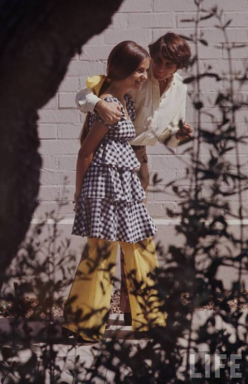 A teenage girl in a cute sundress and yellow bell-bottoms and her boyfriend walk in an image from Life magazine photographer Arthur Schatz's photo-essay on high school fashion in 1969.