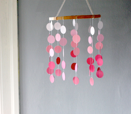 dannaklein:  Paint chip Hanging Mobile - grab an embroidery hoop from you nearest craft store, decide on a shape and cut out varying sizes. Punch holes and string the pieces through, tying the top of the string around the embroidery hoop. Pick up a ceiling hook and you've just made your own wonderfully fun mobile!
