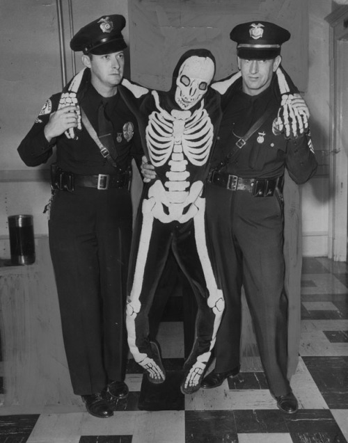 "Two Los Angeles policeman and a skeleton named ""Mr. Statistic"" attempt to warn drivers about traffic fatalities during Labor Day weekend. Shot around 1952."