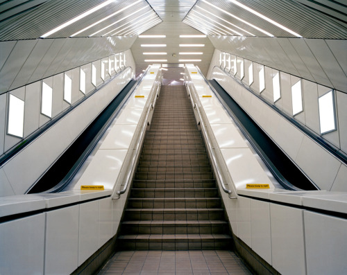 Underground. From the series Adrift in Capitalism © John L Morrison 5x4 Fuji NPL Part of a series exploring the ubiquitous and pervasive presence of advertisements and their influences and interactions with architecture. Focusing on seeing adverts in the everyday spaces I take for granted became a kind of obsession. I wanted to communicated these in a way that borrowed from the vocabularies, seductions and delivery methods of the ads themselves. Using colour, symmetry and showcasing the works on light boxes all helped create a layer of abstraction allowing viewers to observe their everyday world from a different perspective, highlighting the saturated surface of the information economy. It was not until after seeing the photographs on the wall and speaking with the external examiner at Edinburgh College of Art that I realised the significance of the architecture in these spaces. It was almost as if the structures were built to prime us for the excess of information and endless opportunities of individual satisfaction on their symmetrical walls.  The empty cinema image, took on significance for me as representing a place of worship for a new generation. A place which symbolises our love of our own enslavement -more a Huxley world than an Orwellian one. The latest type of social control, one that keeps us spiralling in desires, debt and more desires so we don't concern ourselves with difficult questions, anaesthetised to what is truly important.  I was 20 years old when making these images and now more than 10 years later the naiveté of my ideas are a lot more apparent to me. However, I am not yet done with this project and although have become somewhat a victim of the Ikea nesting myself, discovering books like John Berger's seminal Ways of Seeing has re-ignited a desire to make photographs true to the documentary spirit of visual communication.