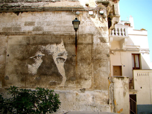 everydayfrustone:  Alexandre Farto aka Vhils   Using abandoned and depleted buildings as his canvas, Alexandre creates fascinating large scale portraits by carefully scratching and chipping plasters out of walls. Alexandre Farto, better known as Vhils, is a Portuguese street artist based in London. Born in 1987, he gained prominence when his work of a face carved into a wall appeared alongside a picture by street artist Banksy at the Cans Festival in London in 2008. A photograph of him creating the work appeared on the front page of The Times. He was later given space to show his work by Banksy's agent, Steve Lazarides. Several of his works were featured in Outsiders, a collection of street art published by Century, 2008