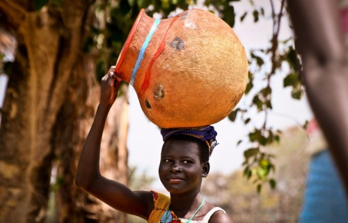 A village woman carries a pot to the market in Lira district, north of Uganda's capital, Kampala. Photography by Echwalu Photography .