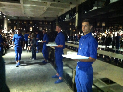 Handsome men in blue boiler suits and matching brogues serving drinks at Acne #LFW