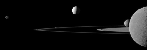 itsfullofstars:  Cassini Presents Saturn Moon Quintet   With the artistry of a magazine cover shoot, NASA's Cassini spacecraft captured this portrait of five of Saturn's moons poised along the planet's rings. From left to right are Janus, Pandora, Enceladus, Mimas and finally Rhea, bisected by the right side of the frame. The view was acquired at a distance of approximately 684,000 miles (1.1 million kilometers) from Rhea and 1.1 million miles (1.8 million kilometers) from Enceladus. The image was taken in visible green light with the Cassini spacecraft narrow-angle camera on July 29, 2011. Image scale is about 4 miles (7 kilometers) per pixel on Rhea and 7 miles (11 kilometers) per pixel on Enceladus. Read more.