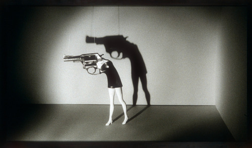 "cavetocanvas:  Walking Gun - Laurie Simmons, 1991 From the Heilbrunn Timeline of Art History: In the early 1990s, Simmons created wickedly funny large-format photographs showing spotlit doll legs topped with various toy-objects: revolvers, houses, cameras, and cakes. By aping the scale and impact of billboards and movie screens, Simmons turns the ""directorial"" mode of slick staging and lighting against itself, to reveal the spectacle of ""woman-as-object"" in contemporary culture. Sending up the old-movie trope of representing the man creeping in shadow carrying a gun, the artist offers instead the death-dealing seductress of film noir in miniature, a doll capable of killing its master at a moment's notice."