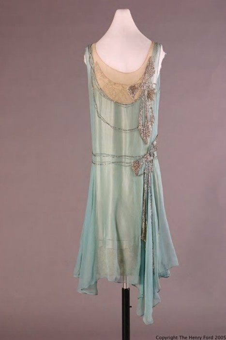 "ornamentedbeing:  ""Dress of turquoise silk georgette over aqua crepe-backed satin. Aqua lace embroidered with gold thread at hem and neckline. Large rhinestone applied bows on left side. Dropped waistline and a slightly uneven hem with longer panels on left side. Machine and hand sewn… . This dress is notable for its gorgeous styling, dramatic color, dipping hemline - which would be quite showy on the dance floor - and fabulous matching shoes with heels studded with brilliants (object number 89.492.560). The American designer, Peggy Hoyt, billed herself as ""Dressmaker to the Aristocracy."""