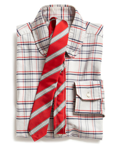 """Thom Browne's always putting a different spin on the dress shirt every season. He's doing something that's a real hybrid that I haven't seen that much, which is a button-down club collar. He finds a new way to reinvent the American button-down every season. This one we love because it's a two-color windowpane pattern so you're going to want to wear this with your quieter fabric suits and tweeds and sportcoats or a solid color cardigan. The tie is silk but it's beefier, it's heavily constructed and it will tie really stiff, with a strong dimple. I haven't seen the red power tie, or the red tie, since the '80s. This is the anti-Republican power tie.""  Shout out to:rubenhughes"