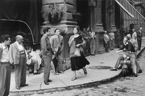 "dodgenburn:  Ruth Orkin (1921-1985, USA) - American Girl in Florence, Italy, 1951 On August 22, 1951, on the Piazza della Repubblica in Florence, Ruth Orkin, a 29 year old aspiring photojournalist, took the photograph that made her famous. The image of a young woman walking through a thicket of men was considered risqué in its time but since then it has become one of the most famous pictures taken.The image is such a perfect and classical composition that some critics to question whether or not the scene was staged. Orkin never hid the fact that the shot was not entirely spontaneous, and spoke of having directed some minor elements of the scene. Whether ""real"" or not, the image remains an icon of street photography to this day.  In Florence Orkin had met Ninalee ""Jinx"" Allen Craig, an art student and fellow American who became the model for a series Orkin originally titled Don't Be Afraid to Travel Alone, based on their joint experience as women travelling alone in Europe in the 1950s. Orkin photographed Craig shopping in the markets, crossing traffic, riding a carriage and flirting at a cafe. By chance the two came upon the now famous pack of men. Orkin turned around and photographed Craig behind her. ""I clutched my shawl to me because that sheaths the body,"" says Craig. ""It was my protection, my shield. I was walking through a sea of men."" Craig today admits, ""I was enjoying every minute of it. They were Italian and I love Italians."" Orkin asked Craig to walk through again, and with that she captured the famous image. It took only two exposures. The photograph was first published in Cosmopolitan magazine in 1952 and it was later it was picked up by Kodak to encourage young photographers."