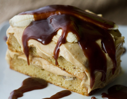 "yummyvegan:  Elvis Cake - the Peanut Butter and Banana King Elvis Cakemakes one cake (two ""sandwich"" style halves, optional) Banana Cake:1 box vanilla cake mix (or see note above)1 large ripe banana, smashed2/3 cup vanilla frosting (my egg replacer, subbed for 3 eggs)2/3 cup soy milk1/2 cup canola oil1/2 tsp cinnamon Peanut Butter Frosting:1 stick of softened vegan buttery spread (my butter replacer)1 box vanilla frosting mix (or from scratch mixture)1/4 tsp cinnamon3/4 cup peanut butter Chocolate Caramel Sauce (recipe here)1 ripe banana, thinly sliced – for garnish and layering Directions: 1. Preheat your oven to 350. 2. Combine your cake batter as directed – fold in the smashed banana last. Pour into greased cake pans – and bake as directed – until the center is fluffy and baked through. I used two small rectangle baking dishes. 3. Cool your cakes. And whip up your frosting with a hand mixer. Place in fridge to chill. 4. Prepare your chocolate caramel according to recipe instructions. Cool in fridge until ready for drizzling. 6. Assemble your cake! (If you want the 'cut sandwich' look you will need to slice each cake and pair it with its half – as I did in photos). Place the first layer on your serving platter. Frost. Add a few slices of banana to the center of the cake. Then add top cake layer over top. Finish frosting the entire cake and top with the remaining sliced bananas. Store in fridge until ready to serve. 7. Serve by drizzling chocolate caramel over top. (via babble)"