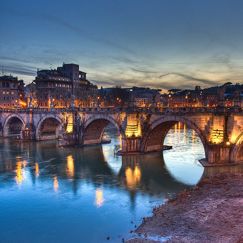 Ponte Sant'Angelo, which means the Bridge of Hadrian. This beautiful Roman bridge that spans the Tiber River connects the Vatican to Castel Sant'Angelo. Completed for the first time nearly 1,900 years ago by Emperor Hadrian, the bridge has served several purposes through the years. It has long been used by people on pilgrimage to the Vatican — one last beautiful leg before reaching their destination. For hundreds of years after the 16th century, the bridge was used to display bodies of executed people. Now the bridge is for pedestrian traffic only, and it sees plenty of tourists as they cross from one attraction to the next. Source: Pont Sant'Angelo wiki allthingseurope:  Ponte Sant'Angelo, Rome, Italy (by paperinikkio)