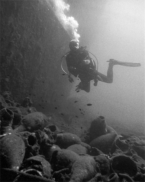 the wall behind the diver is the starboard of mirna-m,the ancient pottery below the diver is called amphora.the amphoras belong to a wreck which was a 7th. century byzantine cargo ship,and the cargo was wine from 7th. century..George Bass and his team finished their archeological study on the wreck at 1964 and a lot of amphoras that were used to carry wine, have been  moved to the Bodrum Underwater Museum for exhibition. 39m. yassı island,turgutreis-bodrum.