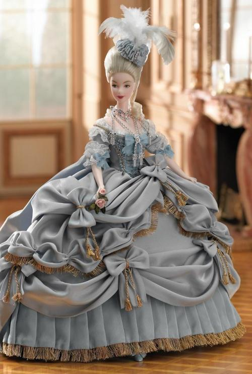 timestar20:  Carrying a handcrafted porcelain pair of roses, Barbie® doll is the height of royalty as Marie Antoinette who became the Queen of France when her husband was crowned King Louis XVI in the 18th century. She wears a regal blue gown and matching bodice that is embellished with touches of golden lace. Draped with golden fringe, the generous layers of her extravagant gown are decorated with golden tassels and hide her full-length pantaloons and the blue satin ribbons on her shoes. A matching hat topped with feathers completes her ensemble. She wears an extravagant rhinestone necklace that complements her dramatic ensemble.