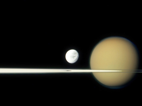 spacettf:  Dione and Titan (9-17-11) by Lights In The Dark on Flickr. Via Flickr: Saturn's moons Dione and Titan lined up with the planet's rings, seen here nearly edge-on, from the point of view of the Cassini spacecraft's camera on September 17, 2011. This is a composite of three raw images taken with Cassini's red, green and blue visible-light clear filters.  Dione, 700 miles wide, is dwarfed by the much larger and further moon Titan, which is over 3,200 miles wide and wrapped in a thick opaque atmosphere. Also in this image is the 12-mile-wide shepherd moon Pan, barely visible within the Encke Gap in the A ring, just below and to the left of Dione. Cassini was about 1.33 million miles away from Dione when this view was acquired. Credit: NASA / JPL / SSI. Edited by Jason Major.www.lightsinthedark.com