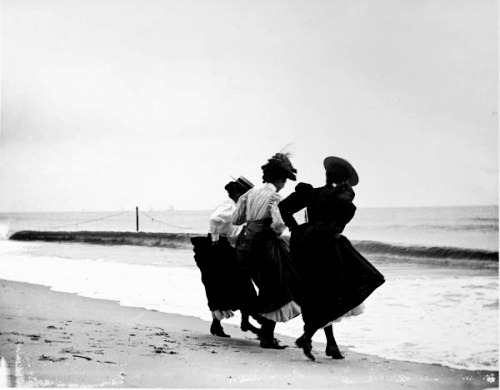 Three fully-clothed women hiking their skirts at the shoreline of the beach in Averne, Wallace G. Levison, 1897
