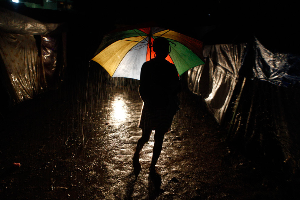 A woman walks with an umbrella at a homeless  earthquake survivors camp during heavy rains in Port-au-Prince,  Saturday, Feb. 27, 2010. (AP Photo/Esteban Felix)