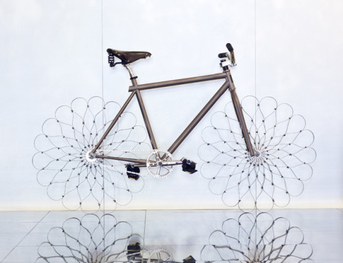 "rozanes:  ReCraft Your Ride: Flower Bike by WOW Bikes For W Hotels' ""WOW Bikes,"" Ron Arad designs a bespoke bicycle that reimagines the wheel using nothing but curved sprung steel. And anyone who stays at the hotel can ride it. The wheel uses 18 individual strips of steel that are pinned at various tension points to act together as one single unit. ""We've actually done very little with the material,"" Hearst tells Co.Design. ""When you bend that steel, the way you pin it, you create natural curves. It's almost like a flower."" The adjacent ""spokes"" create an additional shape that your eye naturally wants to fill in.—————————————————————————————————Displayed on Recraft 