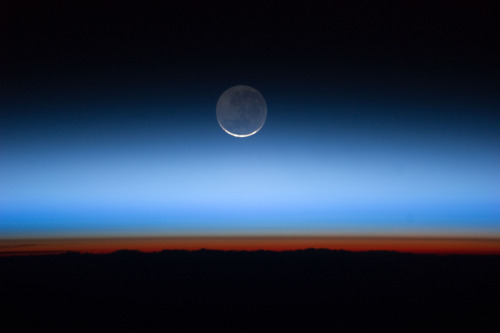 unknownskywalker:  Moon Over Earth Photographed by an Expedition 28 crew member onboard the International Space Station, this image shows the moon at center, with the limb of Earth near the bottom transitioning into the orange-colored troposphere, the lowest and most dense portion of the Earth's atmosphere. The troposphere ends abruptly at the tropopause, which appears in the image as the sharp boundary between the orange- and blue- colored atmosphere. The silvery-blue noctilucent clouds extend far above the Earth's troposphere.  That's no moon! That's a… oh, wait, nope, i'm wrong again. That is a moon. Sorry I keep getting those two confused, folks.
